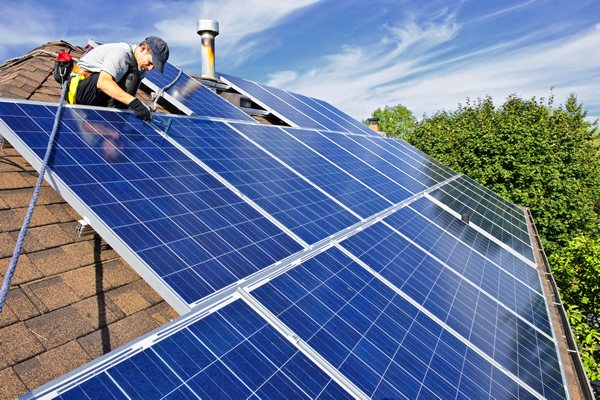 Roofing contractor working on installing solar panels